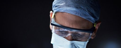 Surgeon wearing surgical mask, cap and glasses