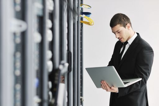 Suited man with laptop in wire room
