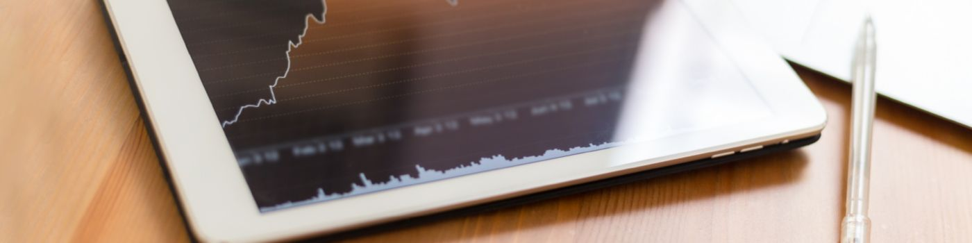 Tablet with line graph and keyboard on table