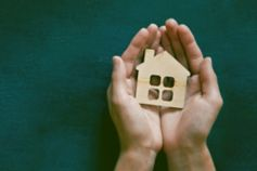 property tax services, hands holding a small wooden house
