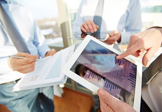 Tablet computers and notebooks being used as hands point to onscreen data