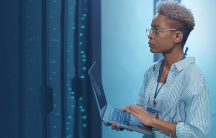 Technician looking over data in a server room while holding laptop