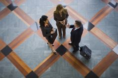 Overhead view of three people standing on grey and orange square floor tiles