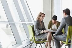 Three business people discussing sitting on green chairs