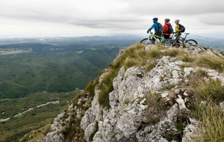 Three cyclist looking at landscape view from top of hill