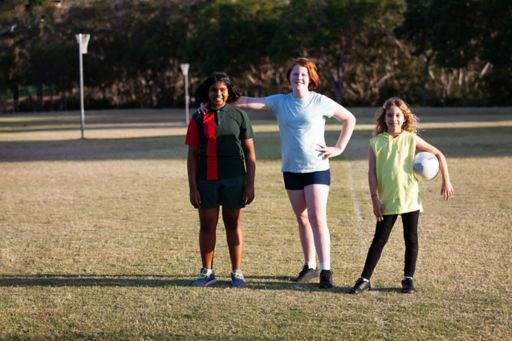 Three resilient girls posing for a community photo in sport outfits