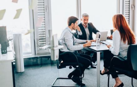 Three people in discussion in meeting room