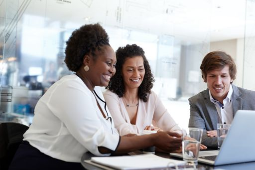 Three smiling business people having meeting in glass room