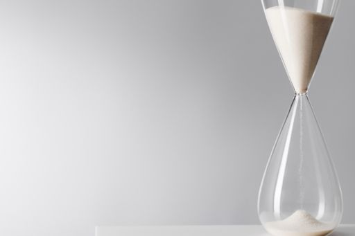 time-hour-glass-against-gray-background