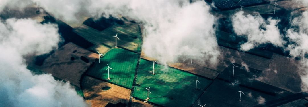 Top view of green field of windmills with clouds