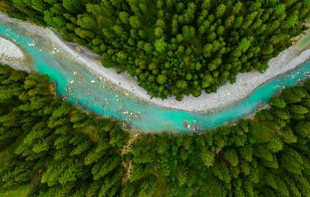 Inn River flowing in the forest in Switzerland. Aerial view from drone on a blue river in the mountains