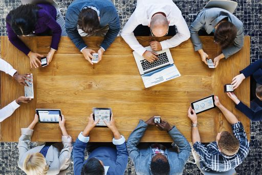 Business people on electronic devices in meeting room