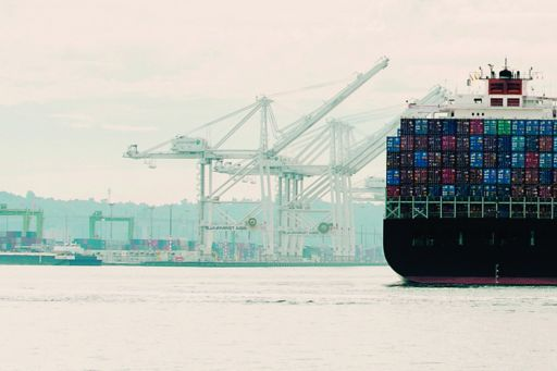 Tugboat and container ship in an industrial harbour