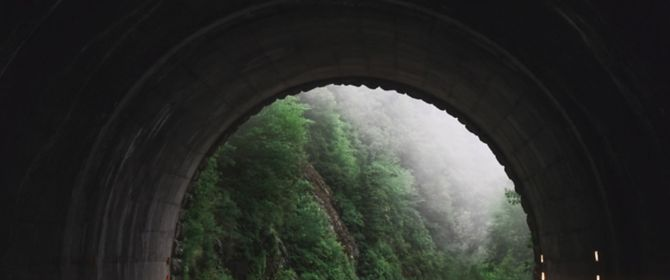 End of a tunnel opening in green foggy mountains