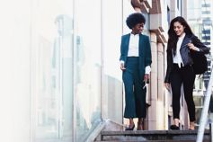 Two business women having a casual discussion while walking