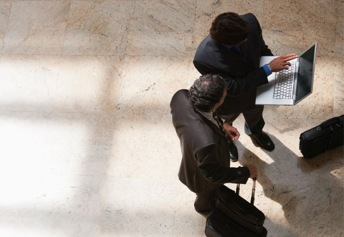 Two businessmen looking at laptop in lobby