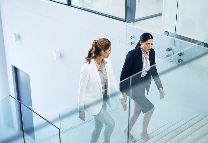 Shot of two businesswomen having a discussion while walking in a modern office