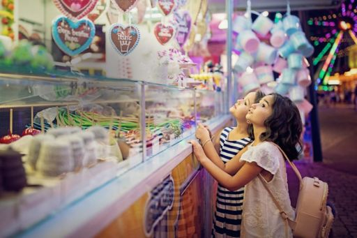 Two little girls looking at sweets at a fun fair