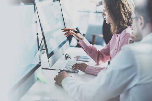 Two people at computer pointing pen to screen