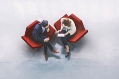 Two people sitting on the red chair discussing something