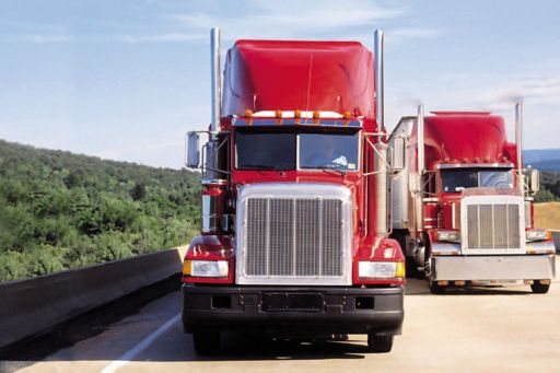 two red carriage trucks driving on the road