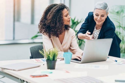 Two women discussing laptop blur background