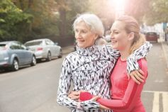 Two women on side of road smiling in the sunshine