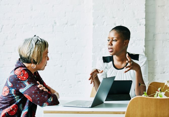Two women talking while working