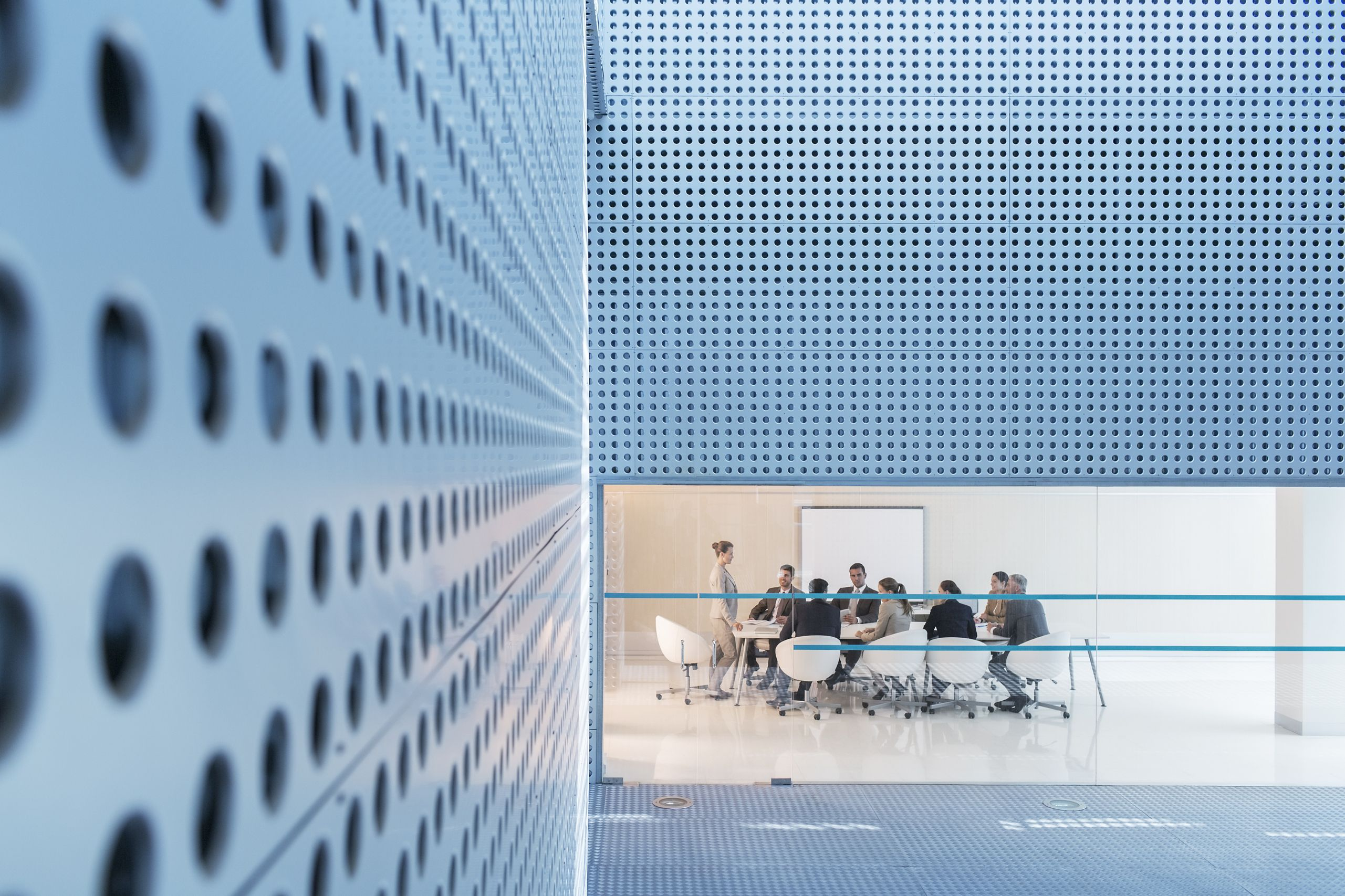 close up of wall with people sitting at an office table in the far distance