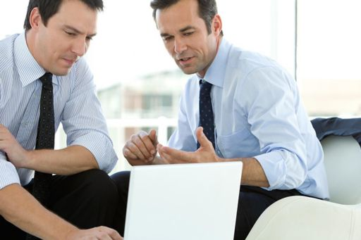 Two men sitting at table looking at a laptop screen