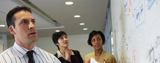 Three people looking at whiteboard