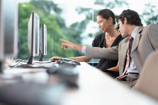 Businesswoman and businessman working on computer
