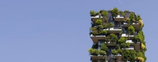 Modern apartment building with green plants on balconies