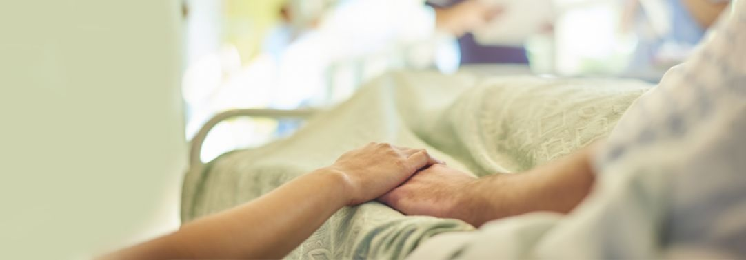 Visitor holds patient's hand in hospital