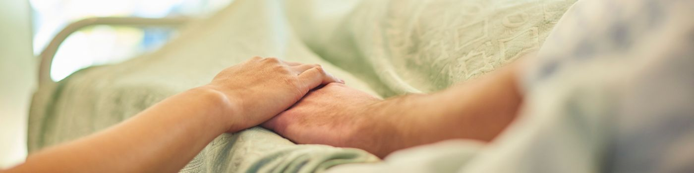 Visitor holds patient hand in hospital