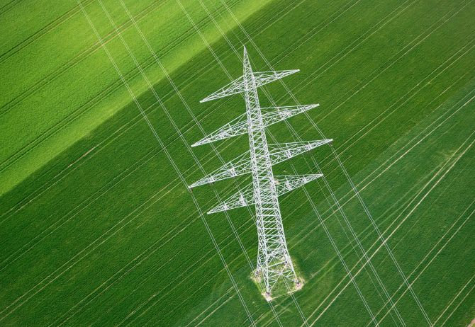 White utility tower in green field