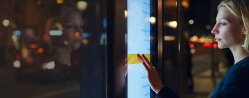 Woman using a touch screen board at night time