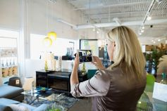 Woman clicking photograph of interior by phone