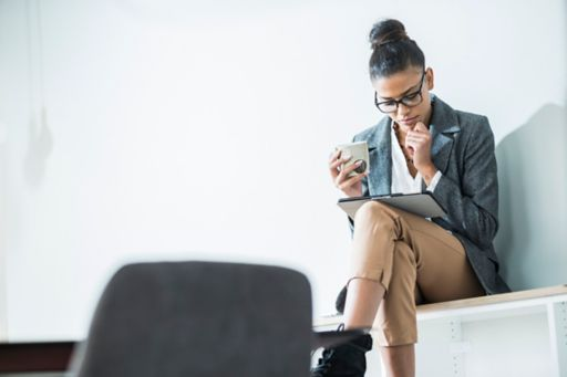 Woman drinking coffee looking at tablet device