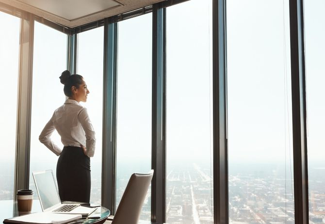 Woman in an office looking outside through the glass window