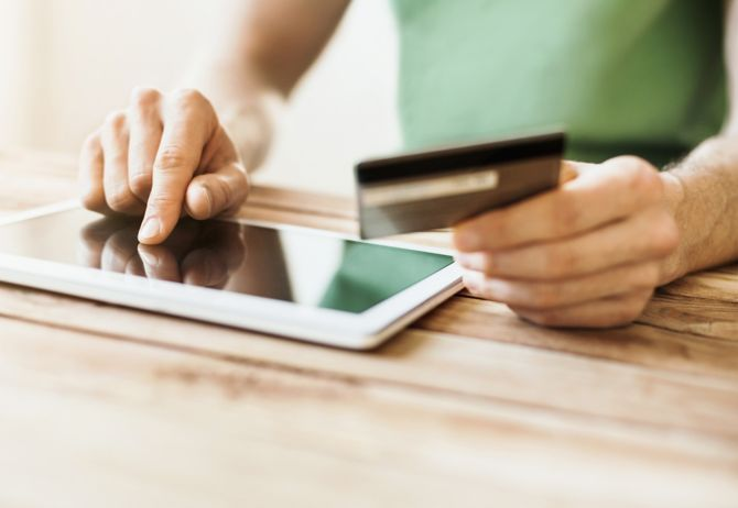 Woman in green shirt paying with credit card on tablet