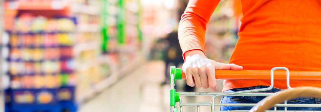 Woman in orange top carrying shopping cart in supermarket