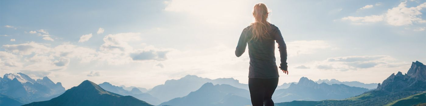 Back view of woman jogging in hilly area
