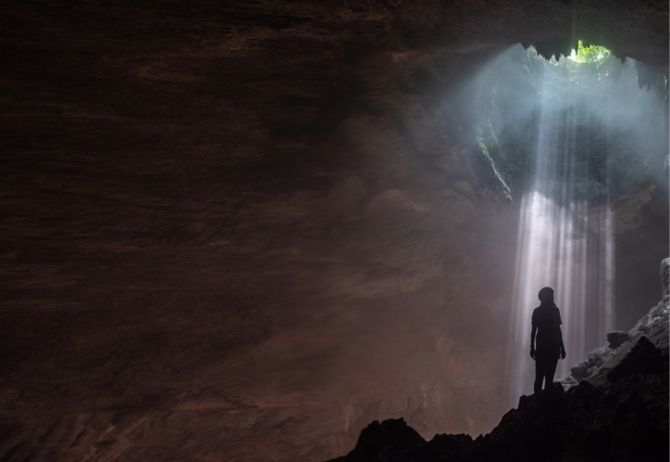 Woman looking up towards light coming in cave