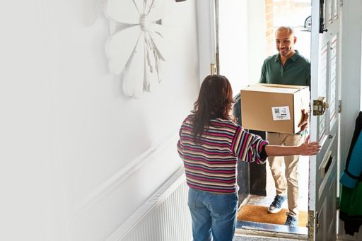woman opening front door to postman with online shopping