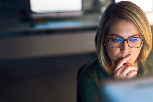 Woman reading the latest OAIC report on data breach notifications on a computer