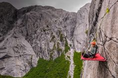 Woman sitting on the board hanging from a cliff