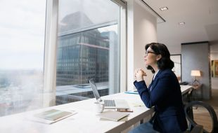Woman sitting with laptop in office