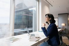 Woman sitting and gazing out of office with laptop in-front