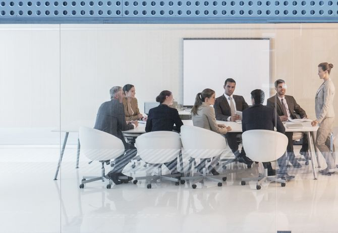 Woman speaking to group of business people meeting room
